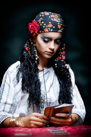 a portrait of a gypsy fortune teller, sitting at a table and