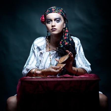 a portrait of a gypsy fortune teller, sitting at a table and mixing the tarot cards that she holds in her hands. she is looking at the camera.
