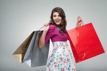 studio portrait of a beautiful young woman, in a colourful outfit, holding in her hands a few shopping bags. she is laughing and looking very happy.の写真素材