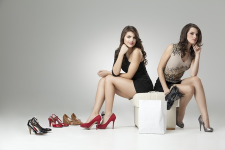Photo for two glamorous women red gray high heels - Royalty Free Image