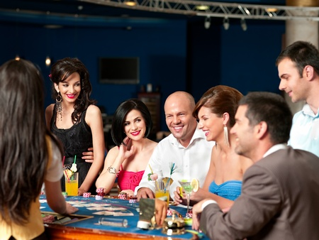 group of people playing blackjack or poker, smiling