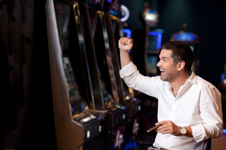 handsome business man just winning at the slot machine