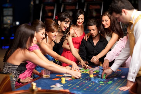 caucasian smiling adults and croupier placing bets