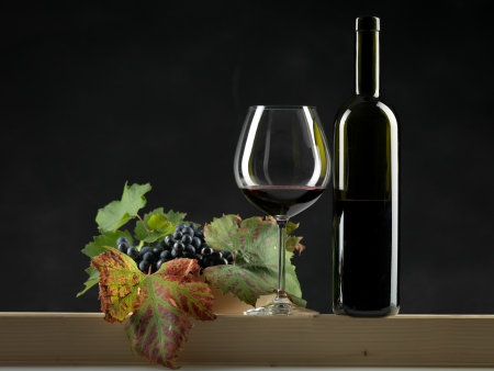 bottle of red wine, glass and bowl of grapes on black background