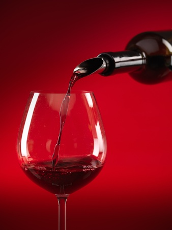 detail of red wine being poured in glass on red background