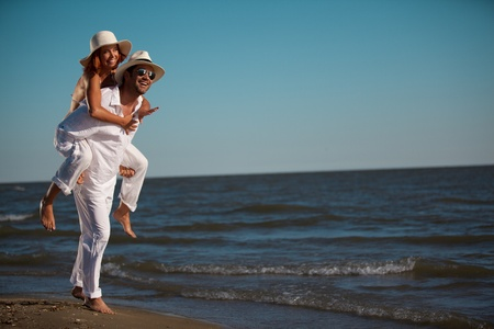 happy young couple dressed in white, on the beach, on a piggy back ride