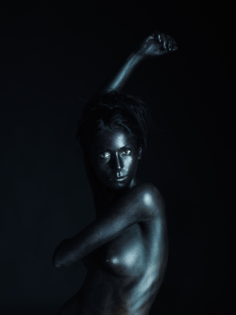 artistic low-key nude portrait of young woman, painted in black, on black background, looking into the camera