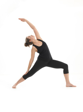 front view of young blonde woman in balanced yoga pose, dressed in black on white background