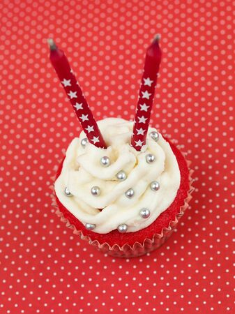 red muffin on red background with white polka dots with two candles seen from above