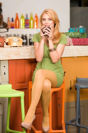 young attractive blonde girl sitting on a chair with her legs crossed near the conter of a colorful cafe with a coffee mug in her hands