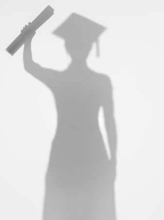 female graduating student standing and proudly showing her diploma, behind a diffuse surface