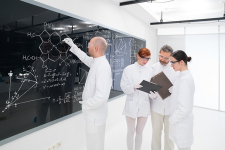 close-up of one scientist in a chemistry lab writing formulas on a blackboard and another three analyzing results on a notebook