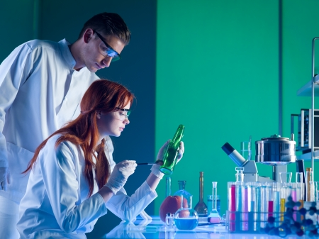 Photo for side view of two forensics scientists taking fingerprints from bottle, in a laboratory - Royalty Free Image