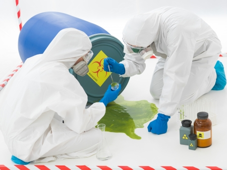 close-up of two specialists collecting samples from a puddle of toxic waste liquid wearing protection suits and masks