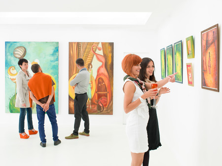 Photo pour people in an art gallery talking about the colorful paintings displayed on walls - image libre de droit