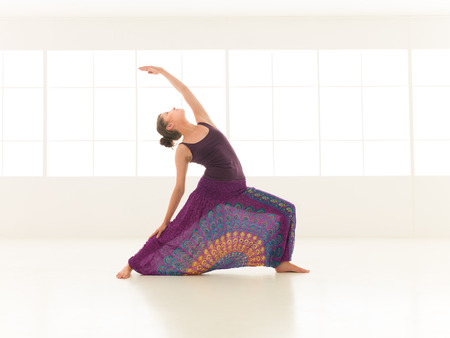 front view of young  woman in balanced yoga pose, dressed colorful indor studio