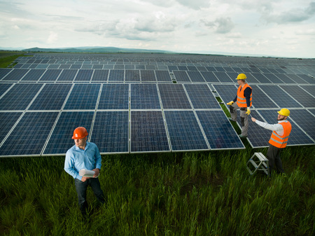 Photo for top view of three men wearing protection equipment inspecting solar panel station, outdoors - Royalty Free Image