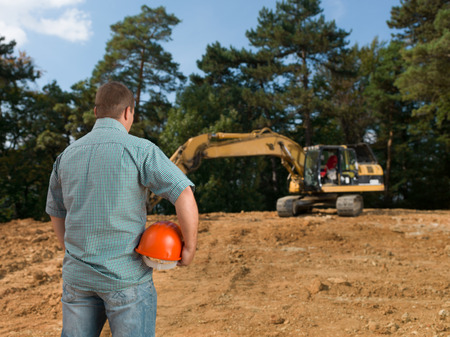 back view of engineer holding hardhat looking at excavator on construction site
