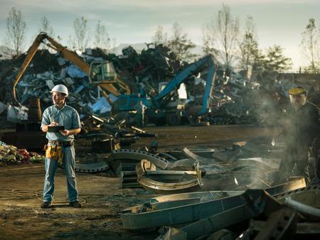 Photo pour caucasian engineer standing at scrap metal recycling site, inspecting work - image libre de droit