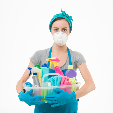 young housewife wearing protection mask, holding cleaning supplies against white background