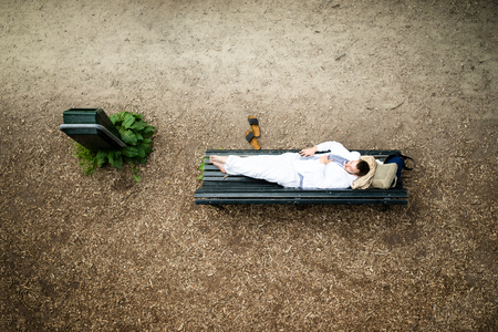 casual dressed man resting on a bench in the park lying on the bench in nature