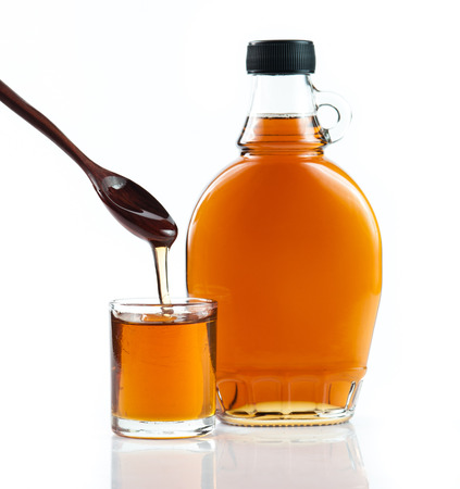 Foto per maple syrup in glass bottle on white background - Immagine Royalty Free