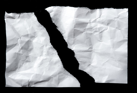 White torn of paper isolated on a black background.