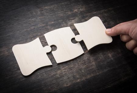Photo pour Hand holding jigsaw puzzles on a rustic wooden,wooden puzzle. - image libre de droit
