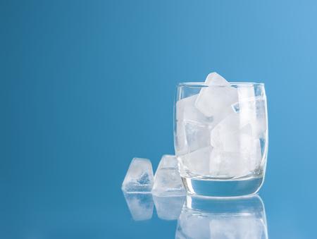 Photo pour Empty glass with ice cube on blue background - image libre de droit