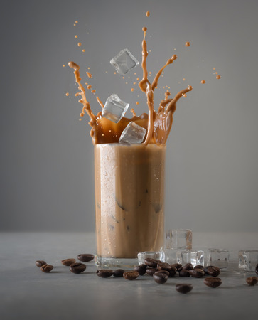Foto de Iced coffee splash with ice cubes and beans against grey concrete - Imagen libre de derechos