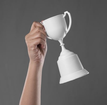 Hand holding up a white trophy cup as a winner on grey concrete wallの写真素材