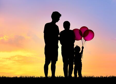 Photo pour Silhouette family,father, mother and children holding balls against the sunset. - image libre de droit