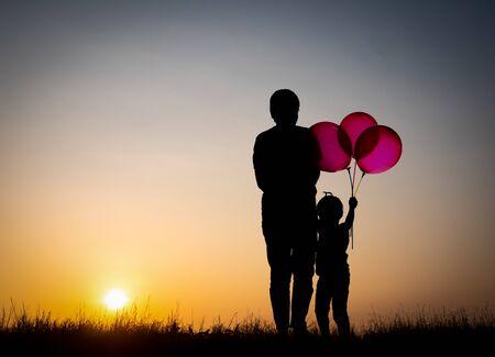 Photo pour Silhouette family,mother and children holding balls against the sunset. - image libre de droit