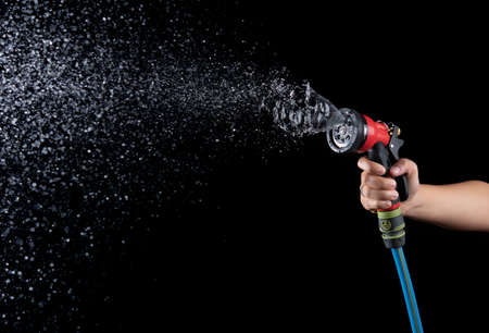 Photo pour Hand hold a gun watering hose with water splash against on black background,spraying hose nozzle - image libre de droit