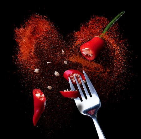 Photo for Red chili pepper on a fork with red chili powder splashing on black background - Royalty Free Image