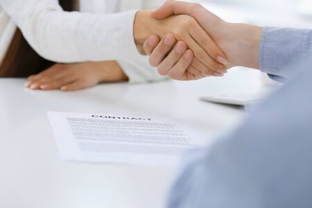 Photo pour Business people shaking hands at meeting or negotiation after contract discussing. Businessman and woman handshake at office while sitting at the desk. Success concept - image libre de droit