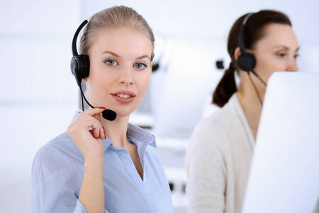 Photo pour Call center office. Beautiful blonde woman using computer and headset for consulting clients online. Group of operators working as customer service occupation. Business people concept - image libre de droit
