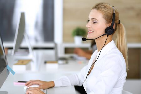 Photo pour Blonde business woman using headset for communication and consulting people at customer service office. Call center. Group of operators at work at the background - image libre de droit