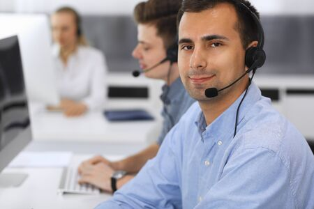 Foto de Call center. Group of casual dressed operators at work. Focus on adult businessman in headset at customer service office. Telesales in business - Imagen libre de derechos