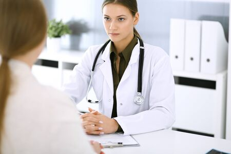 Photo pour Woman doctor and patient sitting and talking at medical examination at hospital office. Green color blouse suits to therapist. Medicine and healthcare concept - image libre de droit