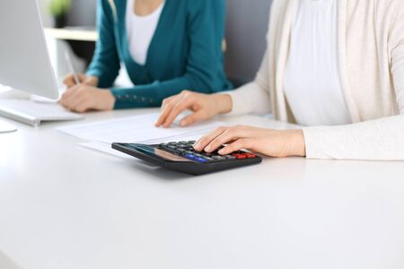 Foto de Accountant checking financial statement or counting by calculator income for tax form, hands close-up. Business woman sitting and working with colleague at the desk in office. Audit concept. - Imagen libre de derechos