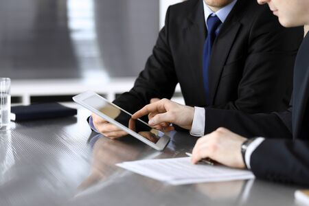 Photo pour Businessman using tablet computer and work together with his colleague or partner at the glass desk in modern office, close-up. Unknown business people at meeting. Teamwork and partnership concept. - image libre de droit