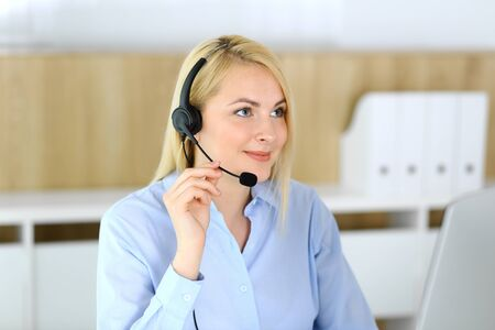 Photo pour Call center. Blonde business woman sitting in headset at customer service office. Concept of telesales business or home office occupation - image libre de droit