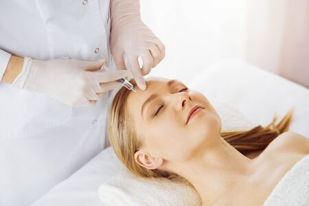 Photo pour Beautician doctor doing beauty procedure with syringe to caucasian female face in synny room. Cosmetic medicine and surgery, beauty injections concept - image libre de droit