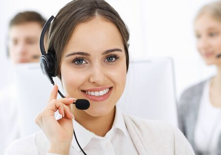 Photo for Call center. Group of diverse operators at work. Beautiful woman in headset communicating with customers of telemarketing service. Business concept - Royalty Free Image