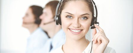 Photo pour Call center. Diverse customer service operators in headsets at work in office. Business concept - image libre de droit