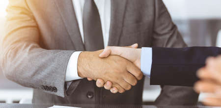 Photo pour Unknown business people are shaking hands after contract signing in modern office, close-up. Handshake as successful negotiation ending - image libre de droit