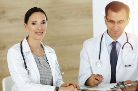 Photo pour Two doctors discussing treatment problems while sitting at the desk in sunny office - image libre de droit