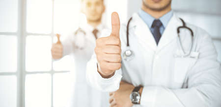 Two male doctors standing as a team with thumbs up in hospital office and ready to help patients. Medical help, best disease treatment and medicine concept