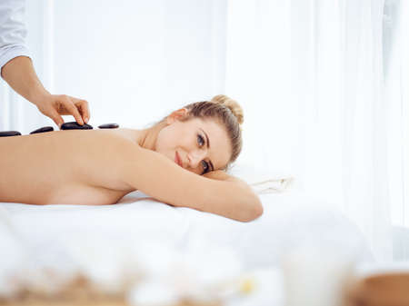 Photo for Young and blonde woman enjoying treatment with hot stones in spa salon. Beauty concept - Royalty Free Image